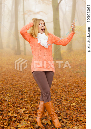 Woman with earphones listening to terrible music. 50308061