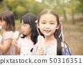 happy children eating popsicle at summertime 50316351