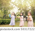 happy little girls playing with water guns on 50317222