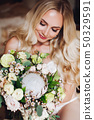 Pretty bride holding wedding bouquet and posing 50329591