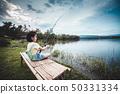 Happy girl pulling rod while fishing against lake. 50331334