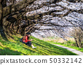 Young woman sitting in cherry blossom garden  50332142