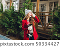 Pretty young girl with long hair in red coat and knitted hat on wooden house background. She holds 50334427
