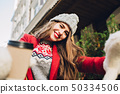 Selfie portrait pretty girl with long hair in red coat on street. She wears knitted hat, white 50334506
