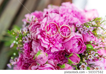 Golden wedding rings on bridal bouquet 50337582