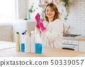 Positive cheerful woman putting on rubber gloves 50339057
