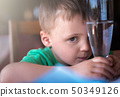 Little boy holding glass with water 50349126