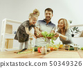 Cute little girl and her beautiful parents are cutting vegetables in kitchen at home 50349326