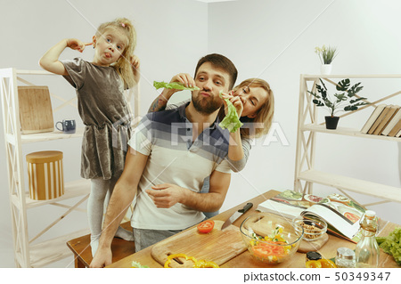 Cute little girl and her beautiful parents are cutting vegetables in kitchen at home 50349347