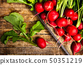Fresh radishes with leaves on wooden table 50351219