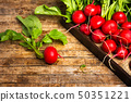 Fresh radishes with leaves on wooden table 50351221