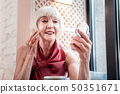 Smiling grey-haired woman with bob haircut examining her makeup 50351671
