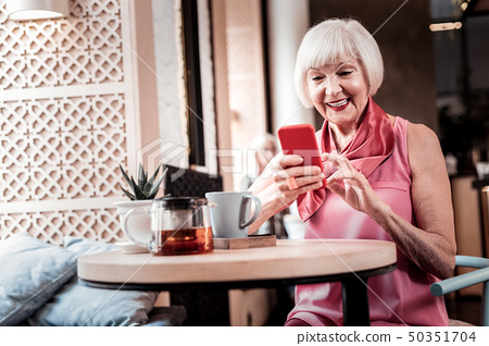 Cheerful old lady comfortably sitting in a cafe 50351704