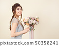 Elegant girl with a haircut in a soft blue dress and make-up is holding a bouquet of a stylish 50358241
