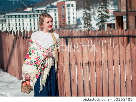 Woman with apples in the snow. Russian style 50365409