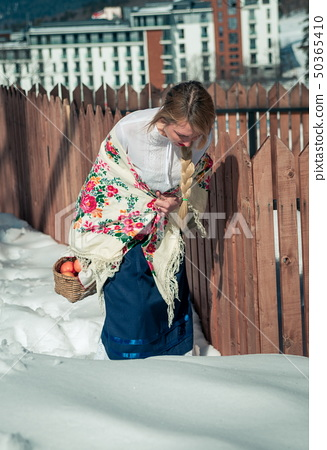 Woman with apples in the snow. Russian style 50365410