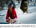 Girl in the snow with apples 50365431