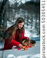 Girl in the snow with apples 50365451