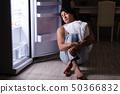 Man breaking diet at night near fridge 50366832