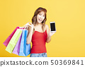 young woman holding shopping bags and smart phone 50369841