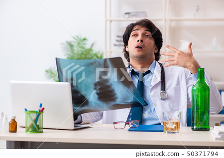 Young male doctor drinking in the office  50371794