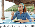 Young woman eating oyster in an outdoor restaurant 50373880