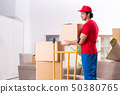 Young male contractor with boxes working indoors  50380765