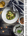 Fusilli pasta with green peas ham and walnuts. 50387788