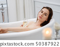 Woman laying in a bath with glass of champagne 50387922