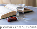 Still life Organic dried dates, cup of drinking water and quran book. Ramadan concept. Selective 50392446