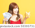 asian woman showing the piggy bank  while holding 50393731