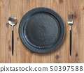 Black plate and table with spoon and fork 50397588