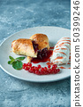 Sliced homemade berry strudel served with fresh red currant berries and powdered sugar on an old 50399246