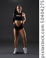 Sporty woman pulling shorts against gray background 50404275
