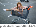 Beautiful girl in the trolley near the supermarket. Autdoor 50404426
