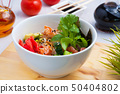 poke salad in a white plate on a wooden Board 50404802