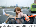 Beautiful girl in the trolley near the supermarket. Outdoor 50405910