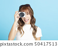 smiling young woman  holding with photo camera 50417513
