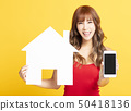 young woman showing  house sign and  smart phone 50418136