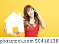 young woman showing  house sign for new home 50418138
