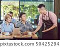 Happy waiter serving couple 50425294