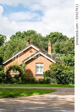 녹색으로 둘러싸인 붉은 벽돌 주택 영국 교외에서 50427611