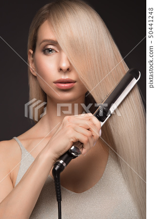 Beautiful blond girl with a perfectly smooth hair, classic make-up with curling styler in the hands. 50441248