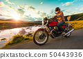 Motorcycle driver riding in Alpine highway, Nockalmstrasse, Austria, Europe. 50443936