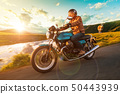 Motorcycle driver riding in Alpine highway, Nockalmstrasse, Austria, Europe. 50443939