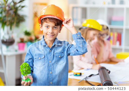 Boy wearing helmet smiling while studying house modeling 50444123