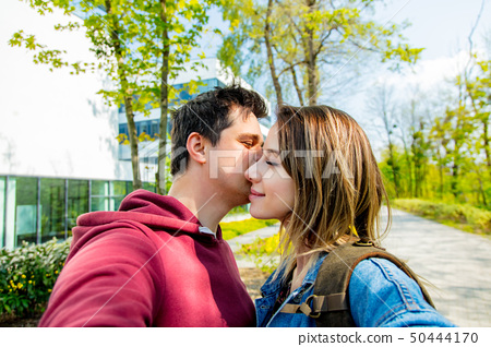 A young couple of Europeans kisses on the street. 50444170