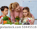 Teacher hugging cute girl while planting flowers with boy and girl 50445516