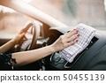 Woman cleaning car dashboard 50455139