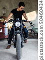 young man sitting on cafe racer motocycle 50460434